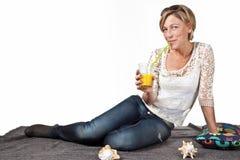 Frau, die im Sommer sitzt auf dem Boden mit einem Glas I sich entspannt Lizenzfreie Stockfotografie