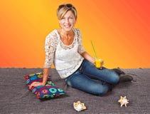 Frau, die im Sommer sitzt auf dem Boden mit einem Glas I sich entspannt Stockfotos