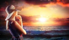 Frau, die im Sonnenuntergang auf dem Meer schaut Lizenzfreies Stockfoto
