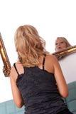Frau, die im Spiegel schaut Stockbild