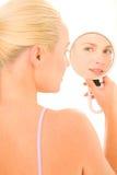 Frau, die im Spiegel schaut Lizenzfreie Stockfotografie
