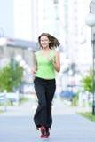 Frau, die im Stadtstraßenpark rüttelt. Lizenzfreies Stockbild