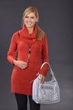 Frau, die im Studio mit Handtaschen aufwirft stockfotos