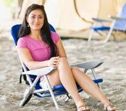 Frau, die im Stuhl am Campingplatz sitzt Stockfotos
