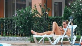 Frau, die im Stuhl durch das Pool ein Sonnenbad nimmt stock footage