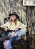 Frau, die im Stuhl mit einem Gewehr sitzt Lizenzfreie Stockfotos