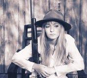 Frau, die im Stuhl mit einem Gewehr sitzt Stockfotografie