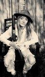 Frau, die im Stuhl mit einem Gewehr sitzt Stockbild
