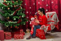 Frau, die im Stuhl mit Weihnachtsgeschenken sitzt stockbilder