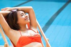 Frau, die im Stuhl neben Swimmingpool sich entspannt Stockfotografie