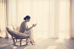 Frau, die im Stuhl sich entspannt lizenzfreie stockfotografie