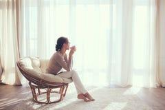 Frau, die im Stuhl sich entspannt stockbilder