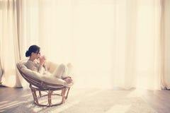 Frau, die im Stuhl sich entspannt lizenzfreies stockfoto