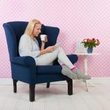 Frau, die im Stuhl sich entspannt Stockfoto