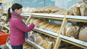 Frau, die im Supermarkt Brot wählt stock footage