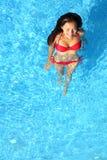 Frau, die im Swimmingpool sich entspannt Lizenzfreie Stockfotos