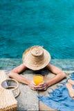 Frau, die im Swimmingpool sich entspannt lizenzfreies stockfoto
