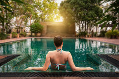Frau, die im Swimmingpool sitzt Lizenzfreie Stockbilder