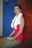 Frau, die im Turnhallenumkleideraum nach Training steht Stockbilder
