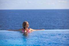 Frau, die im Unendlichkeitspool im Sommer sich entspannt lizenzfreie stockfotos