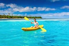 Frau, die im Urlaub im Ozean in der Tropeninsel Kayak fährt Lizenzfreie Stockbilder