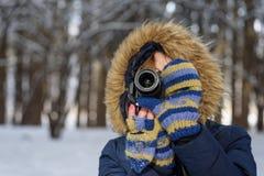 Frau, die im Wald ein Foto mit einer Digitalkamera im Gewinn macht Lizenzfreie Stockbilder