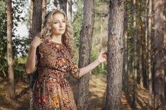 Frau, die im Wald unter den Bäumen in der Natur geht Lizenzfreies Stockfoto