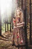 Frau, die im Wald unter den Bäumen in der Natur geht Lizenzfreie Stockbilder