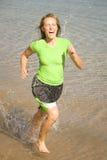 Frau, die im Wasser läuft Lizenzfreie Stockfotos