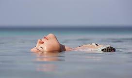Frau, die im Wasser sich entspannt Stockbild