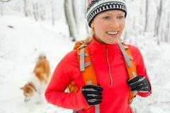 Frau, die im Winter mit Hund wandert Stockfoto