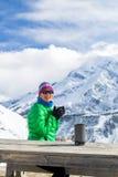 Frau, die im Wintergebirgsniedrigen Lager trinkt Stockfotografie