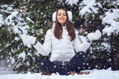 Frau, die im Winterpark sitzt Stockfotos
