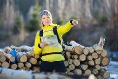 Frau, die im Winterwald mit Karte wandert Lizenzfreie Stockbilder