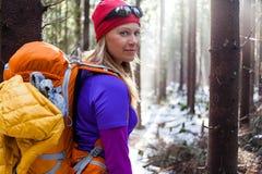 Frau, die im Winterwald wandert Stockfoto