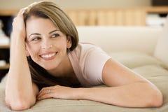 Frau, die im Wohnzimmer liegt lizenzfreies stockfoto