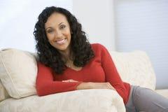 Frau, die im Wohnzimmer sitzt Lizenzfreies Stockbild