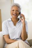 Frau, die im Wohnzimmer unter Verwendung des Telefons sitzt Stockbilder