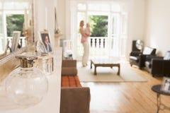 Frau, die im Wohnzimmerholdingschätzchen steht Lizenzfreies Stockfoto