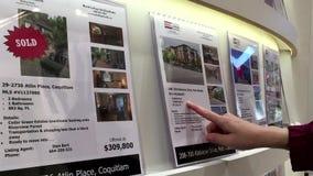 Frau, die Immobilienanzeige über Auflistungshaus für Verkauf liest stock video footage