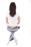 Frau, die innen auf einer Rückseite der Bank sitzt Stockbild