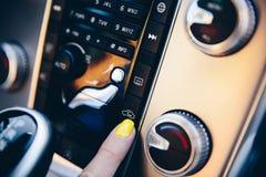 Frau, die innere Zirkulation des Autos einschaltet lizenzfreies stockfoto