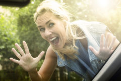 Frau, die inneres Auto schaut und ein lustiges Gesicht macht Stockfotografie