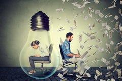 Frau, die innerhalb der elektrischen Lampe arbeitet auf Computer nahe bei Unternehmer unter Geldregen sitzt Lizenzfreies Stockfoto