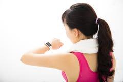 Frau, die intelligente Uhr des Sports betrachtet Lizenzfreie Stockbilder