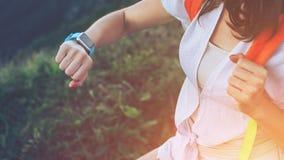 Frau, die intelligente Uhren auf ihrem Handgelenk, während Trekking betrachtet und entlang Bergwiesen geht stockbilder
