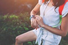 Frau, die intelligente Uhren auf ihrem Handgelenk, während Trekking justiert und entlang Bergwiesen geht stockfoto
