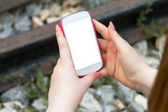 Frau, die intelligentes Telefon auf Eisenbahn hält Stockbilder