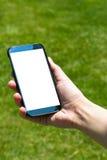 Frau, die intelligentes Telefon auf natürlichem zeigt Stockbild