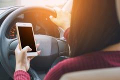 Frau, die intelligentes Telefon beim Fahren ihres Autos auf der Straße, gefährlich verwendet Lizenzfreie Stockbilder